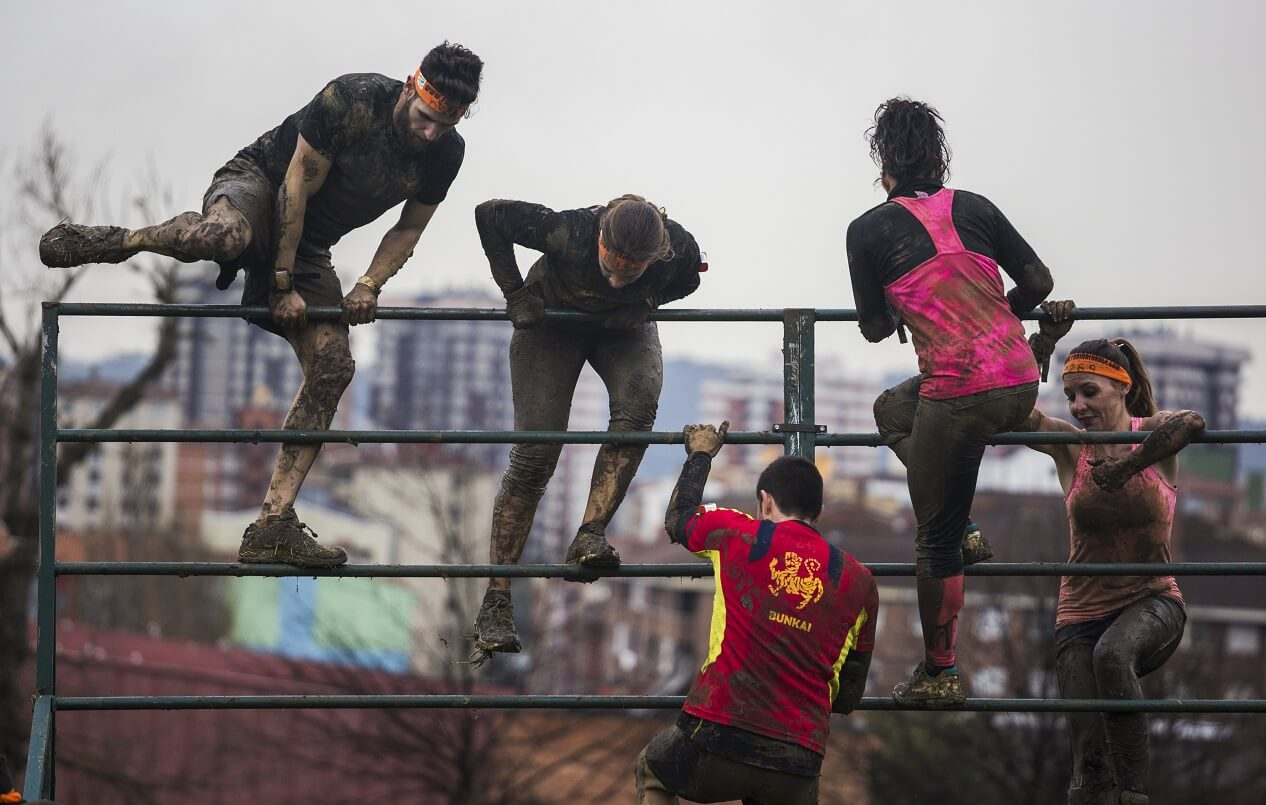 Competitors climbing over bars during obstacle course race