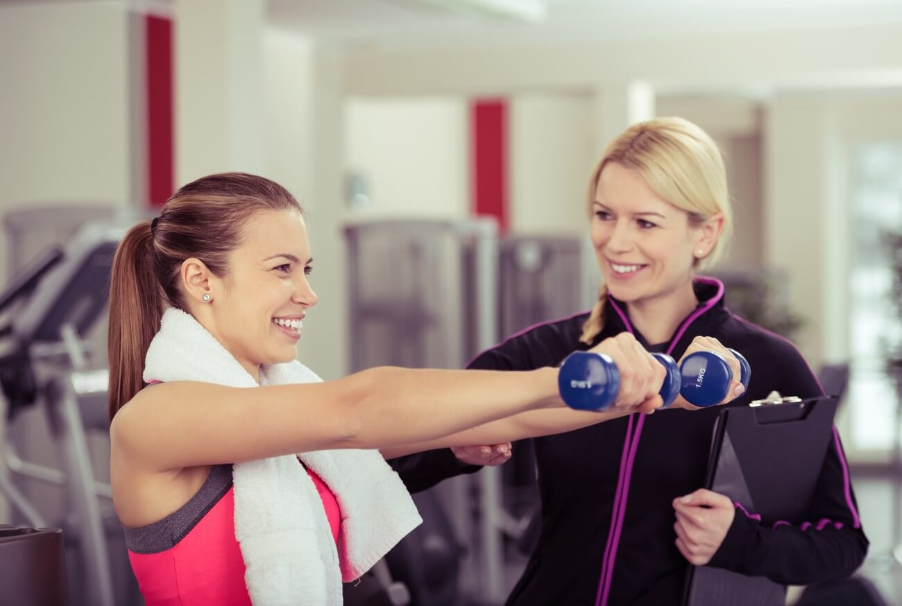 Female personal trainer with client holding weights