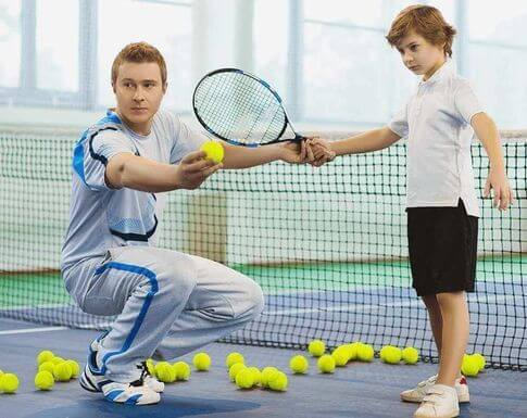 Tennis coach teaching boy how to play