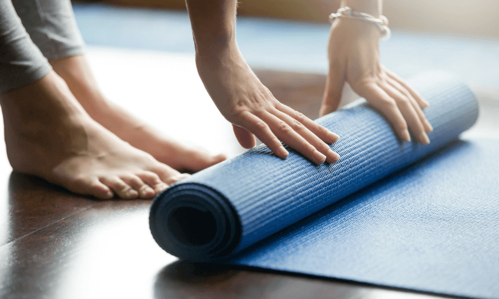Person rolling up a exercise mat